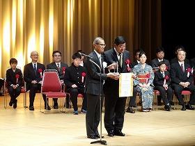 土木学会の磯部雅彦会長から表彰状とトロフィーをいただいた渡辺専務理事